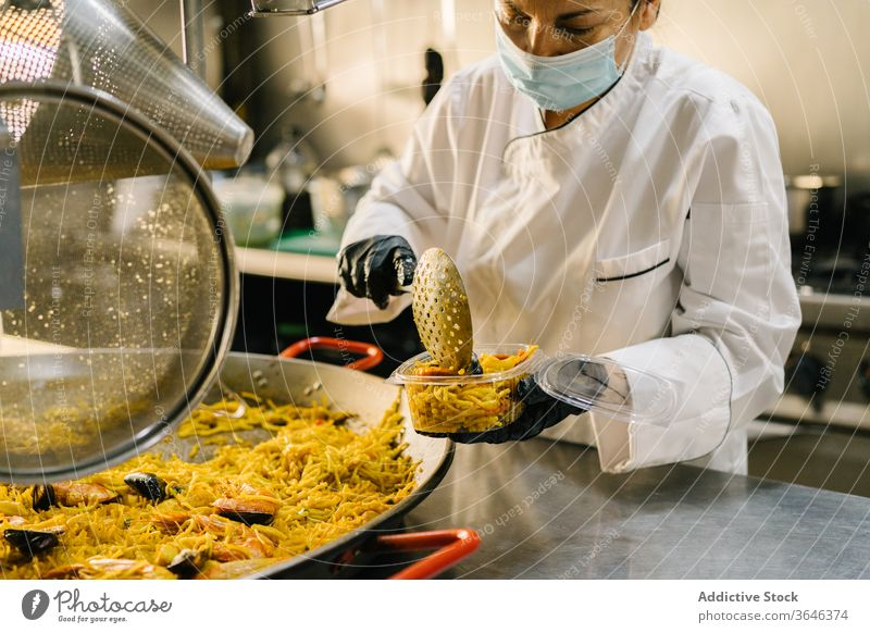 Köchin in Maske verpackt Nudelgericht in Restaurantküche Frau Küchenchef Rudel lecker Imbissbude Atemschutzgerät Meeresfrüchte Versand Kunststoff Konzentration