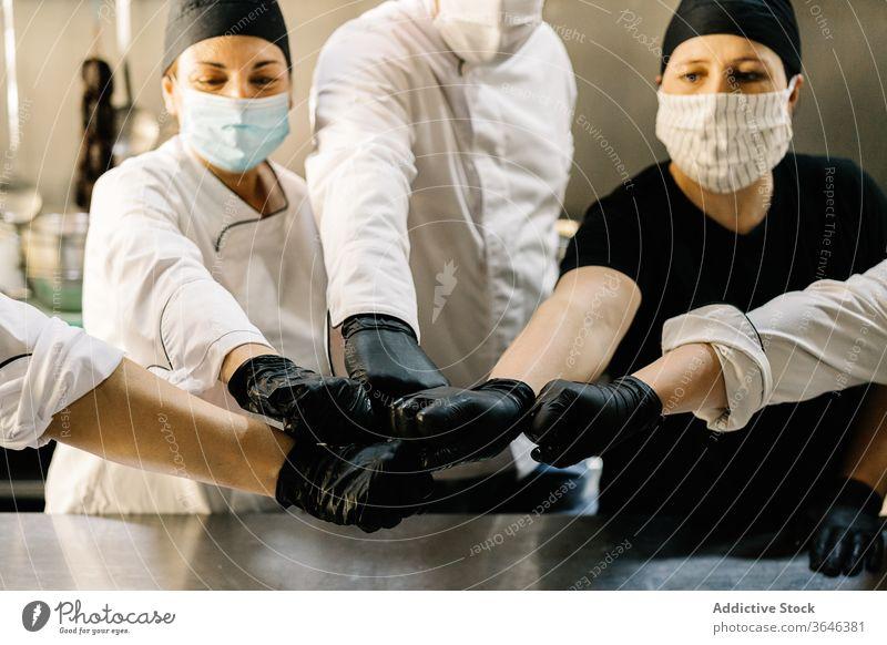 Nutzpflanzenküchenpersonal in Masken schlägt übereinstimmend Hände Küchenchef Personal Atemschutzgerät Schlaghand Team Vereinbarung Handschuh Coronavirus Inhalt