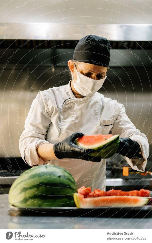 Köchin in Atemschutzgerät schneidet reife Wassermelone in Restaurantküche Frau Küchenchef Scheibe Fokus Uniform Konzentration Handschuh frisch Koch organisch
