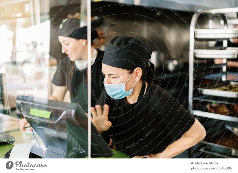 Konzentrierte weibliche Kassiererin mit Gesichtsmaske, die mit der Kasse arbeitet Frauen Arbeit Atemschutzgerät Abfertigungsschalter Café Coronavirus