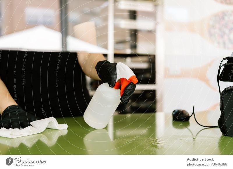 Weibliche Kassiererin in Gesichtsmaske wischt mit einem Tuch die Theke Frau Wischen Atemschutzgerät Abfertigungsschalter Café Handschuh Coronavirus