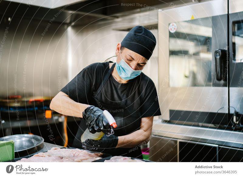 Fokussierte Köchin in Atemschutzgerät, die Fleisch auf Backblech sprüht Küchenchef Frau Spray Erdöl Hähnchen Pfanne Konzentration Coronavirus ernst Koch