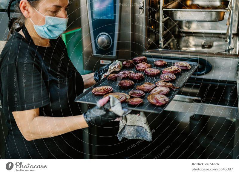 Getreidekoch in Atemschutzgerät mit gerösteter Zwiebel auf Backblech Küchenchef Frau Braten Ofen Fokus Restaurant Coronavirus Bestandteil Lebensmittel Koch