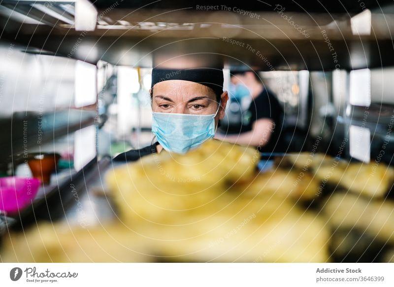 Küchenarbeiterin mit Gesichtsmaske gegen Pfannengestell Frau Küchenchef Lebensmittel Stahl Atemschutzgerät Coronavirus Arbeit Konzentration Zeitgenosse