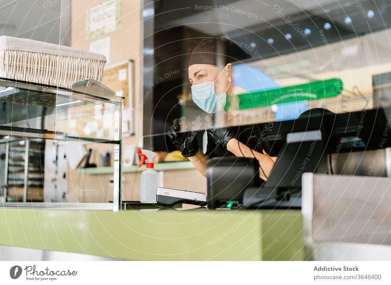 Konzentrierte weibliche Kassiererin mit Gesichtsmaske, die mit der Kasse arbeitet Frau Arbeit Atemschutzgerät Abfertigungsschalter Café Coronavirus