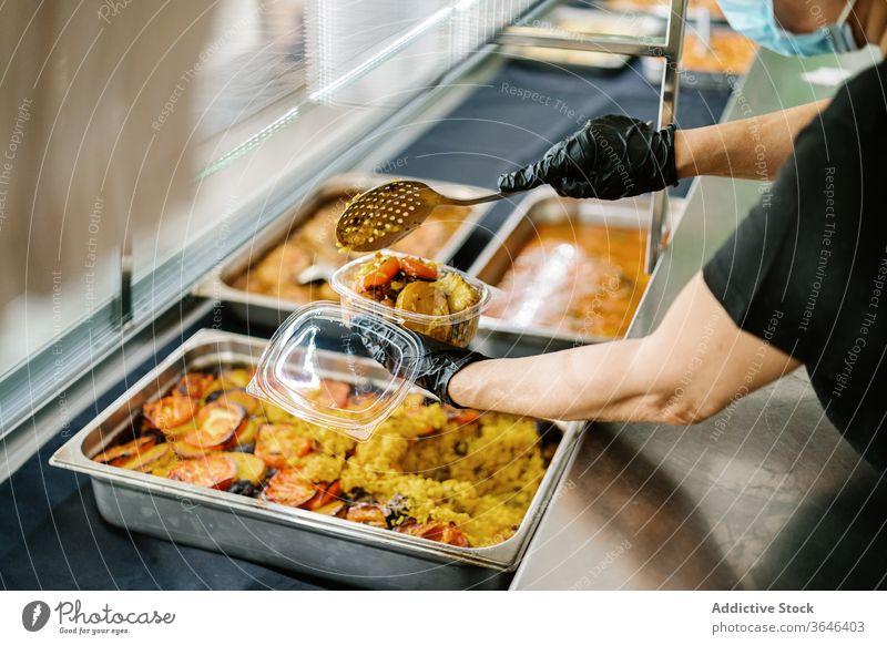 Angestellte in einem Getreidecafé, die Lebensmittel in Plastikbehälter zum Mitnehmen einpacken Kellnerin Atemschutzgerät Rudel Imbissbude Kunststoff Container