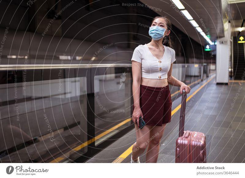 Stilvolle Asiatin mit Atemschutzmaske und Koffer wartet auf den Zug Frau Bahnhof Spaziergang reisen Atemschutzgerät stehen Podest Coronavirus Passagier Bund 19