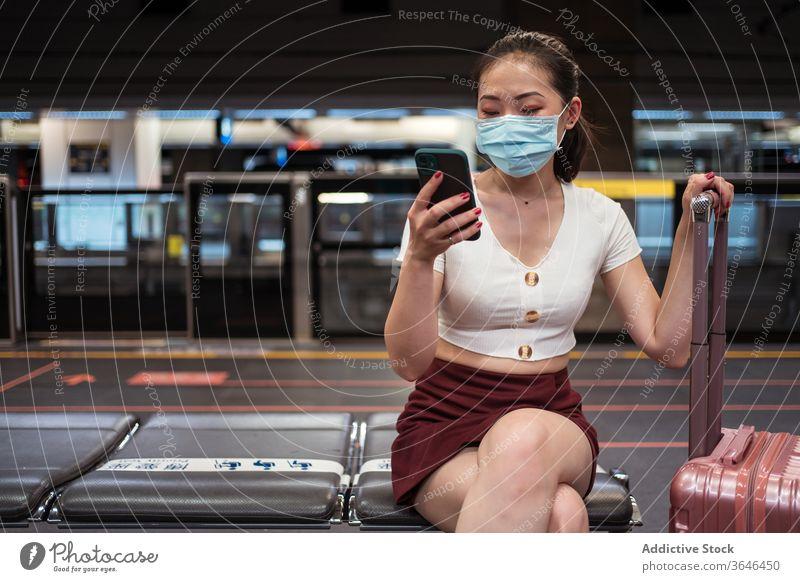 Asiatische Frau in Maske benutzt Smartphone in Flughafen-Zugverbindung benutzend Koffer Station Bahnverbindung reisen Mundschutz Atemschutzgerät Coronavirus