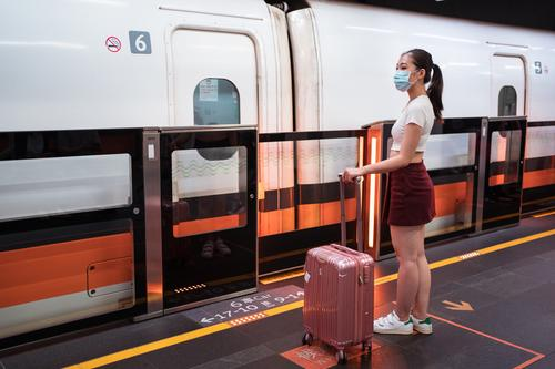 Asiatische Frau mit Beatmungsgerät wartet am Bahnhof auf das Einsteigen in den Zug Koffer Holzplatte reisen Podest Coronavirus Windstille Kabine Passagier