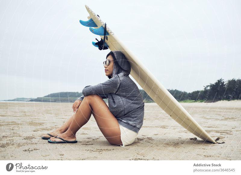 Entspannte Frau sitzt am Strand mit einem Surfbrett auf dem Kopf Surfer ruhen lässig Sand sich[Akk] entspannen sportlich ruhig Sonnenbrille Lifestyle Natur