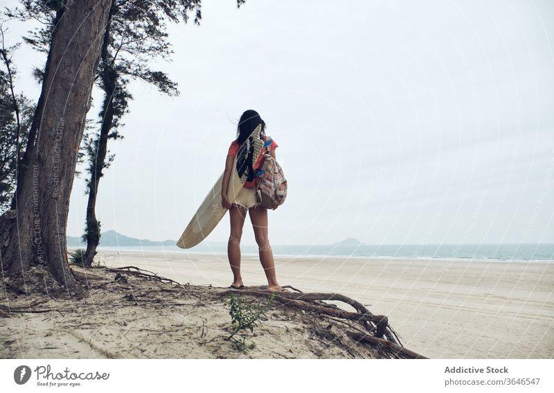 Anonyme Surferin, die mit einem Surfbrett am Strand spazieren geht Frau Spaziergang sandig führen Inhalt MEER lässig Seeküste sorgenfrei Aktivität jung