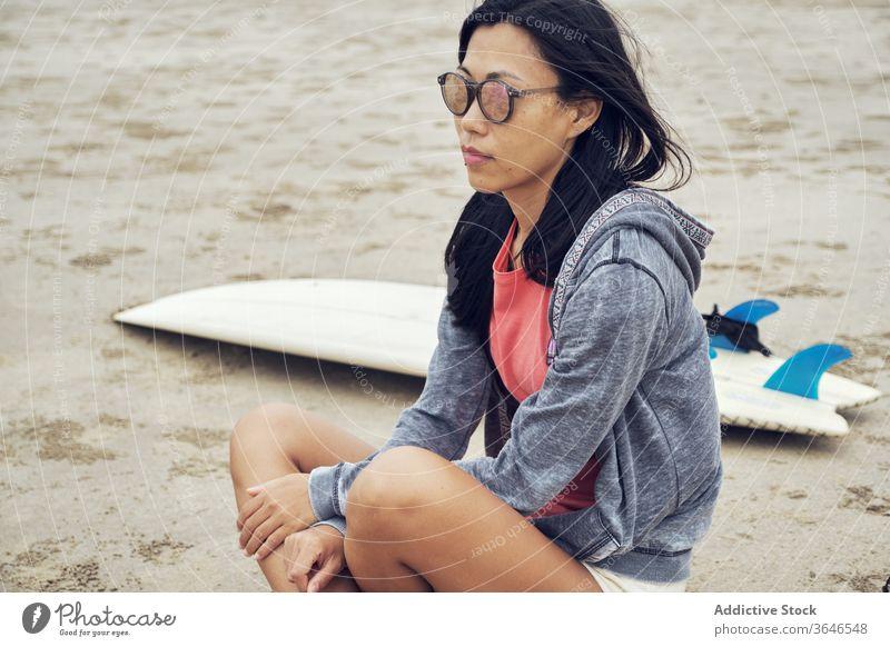 Ruhige Asiatin sitzt am Strand in der Nähe eines Surfbretts Frau Surfer sandig ruhen nachdenklich lässig Sonnenbrille Seeküste sich[Akk] entspannen sitzen jung