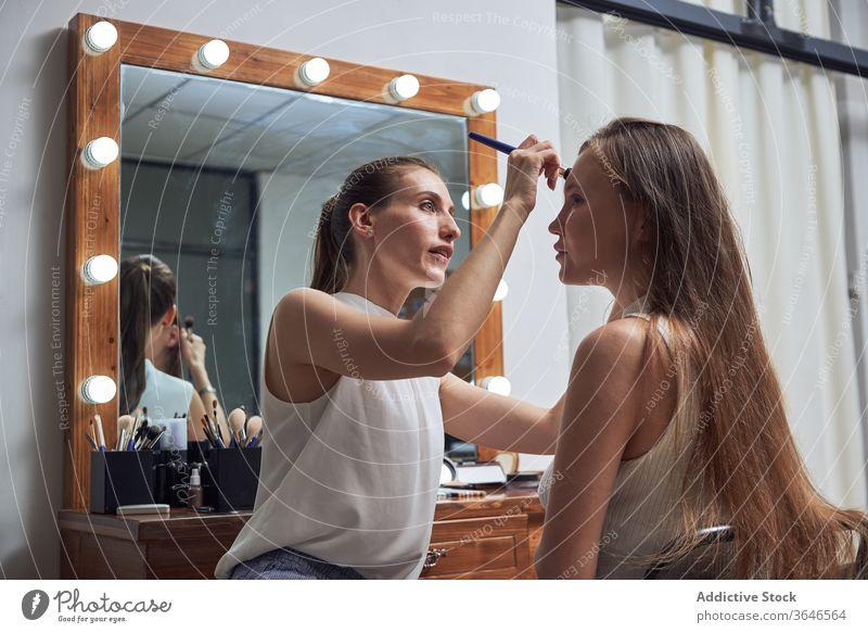 Professioneller Visagist schminkt das Gesicht des Modells visagiste Bürste Make-up Salon Spiegel Licht positiv bewerben Konzentration Kosmetik Klient Pflege