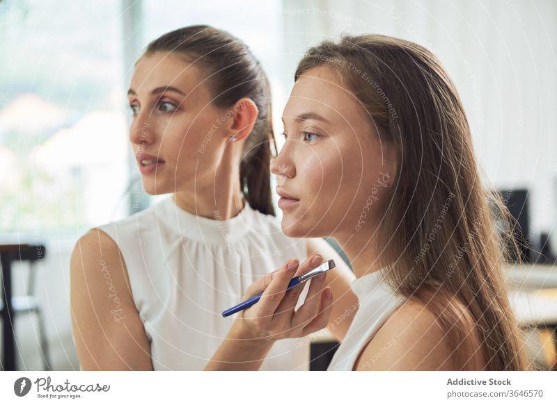 Stylistin beim Auftragen von Eyeliner auf das Modell visagiste Bürste Make-up Atelier Augenbrauen Fokus bewerben Konzentration Klient jung Beruf Kosmetik Pflege