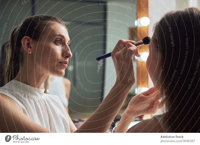 Professioneller Visagist trägt Puder auf das Gesicht des Modells auf visagiste Pulver Bürste Make-up Salon Spiegel Licht positiv bewerben Konzentration Kosmetik