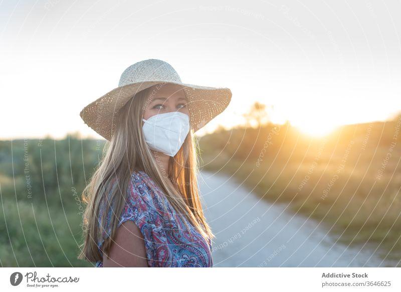 Charmante Frau mit medizinischer Maske auf dem Land Mundschutz Coronavirus Seuche Landschaft genießen Sonnenuntergang ländlich charmant Sommer Straße sorgenfrei
