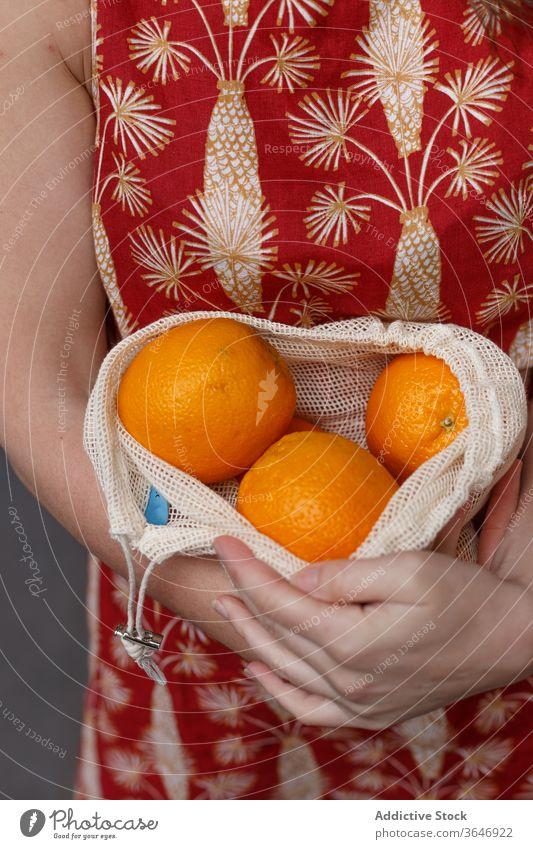 Erntehelferin mit frischen Früchten im Schnurbeutel reif orange Einkaufstasche wiederverwenden Frau Tasche umweltfreundlich gesunde Ernährung Frucht Ökologie