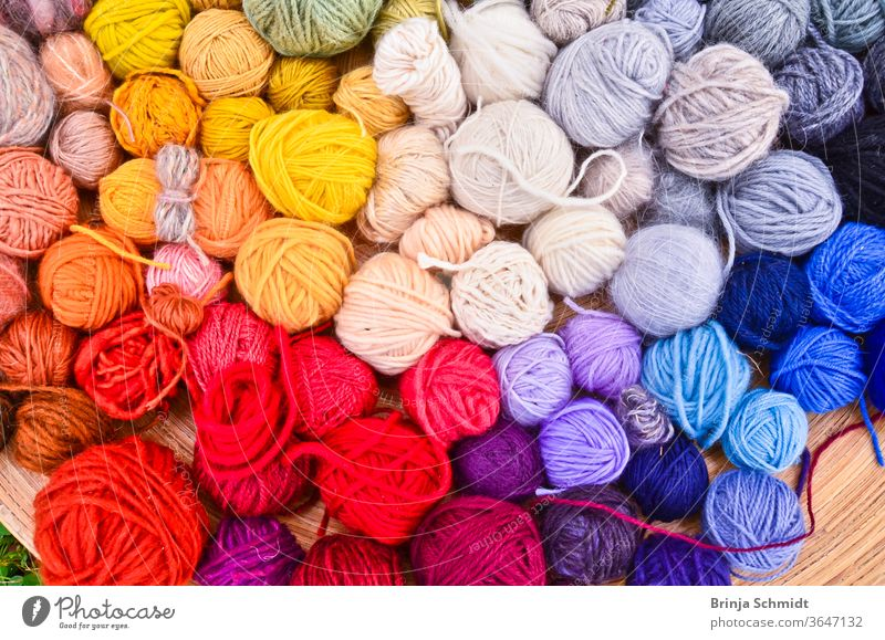 Viele bunte Wollknäule in einer flachen Holzschale auf dem Boden im Gras liegend texture leisure pattern needlework creative textile knit work woven cotton
