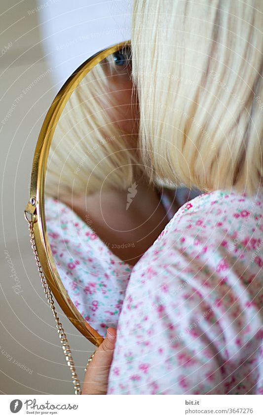 Blondes Mädchen hält zuhause, in heller Wohnung, einen goldenen Spiegel in der Hand und betrachtet, identifiziert neugierig ihr Spiegelbild. Kindliche, spielerische Selbstbetrachtung, Wahrnehmung. Blaues Auge von einem Kind im Spiegel mit Goldrahmen. Zwei.