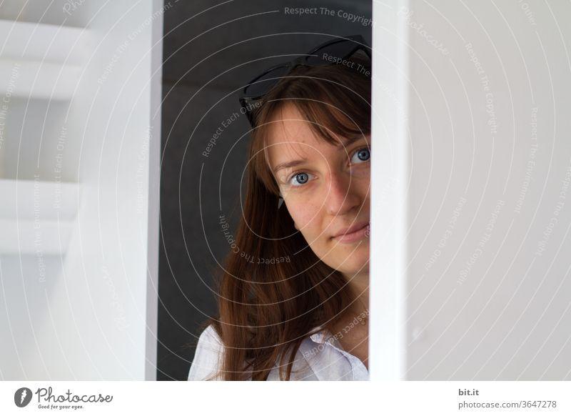 Junge Frau mit Sonnenbrille auf dem Kopf, schaut hinter einer weissen Wand hervor. Hübsche, kulleräugige Frau kuckt neugierig um die Ecke und lächelt sanft in die Kamera. Beautyfotografie zwischen zwei Wänden, zuhause in einem hellen Zimmer der Wohnung.