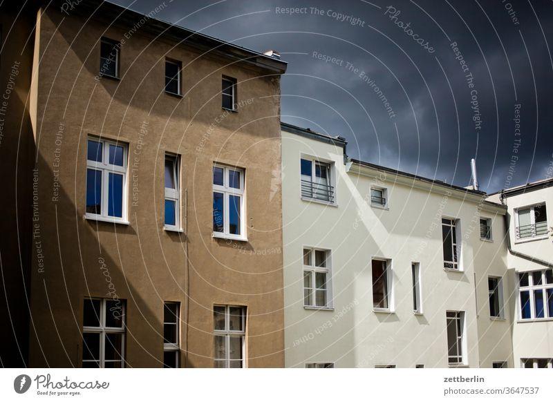 Fassade mit Wolken und Sonne altbau außen brandmauer fassade fenster haus himmel himmelblau hinterhaus hinterhof innenhof innenstadt mehrfamilienhaus