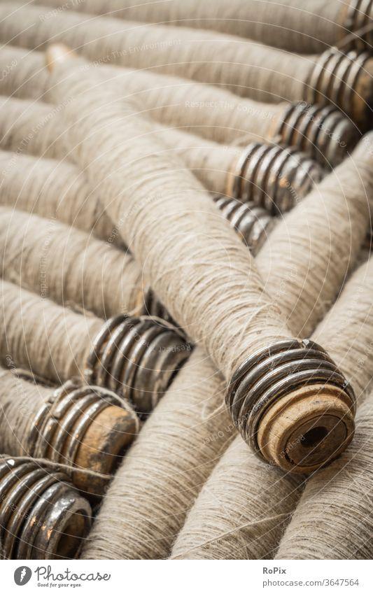 Garn aus Leinen zur Verarbeitung auf dem Webstuhl. spülen rollen Farben bunt gemischt Kabeltrommel Seiltrommel Textil Korbflechten Spinnerei Unternehmen