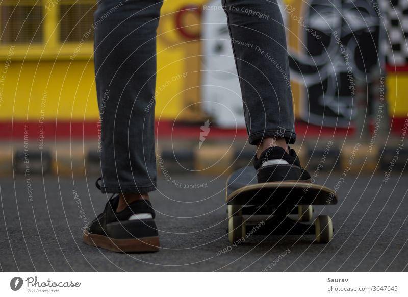 Ein junger Mann steht, während er seinen Fuß auf einem Skateboard hält. Skateboarding Sommer neue Normale Sport Freizeit Lifestyle Turnschuh im Freien