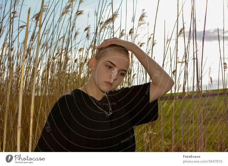 Mädchen mit sehr kurzem Haar in der Natur, Hand oben auf dem Kopf Gras Porträt krank Mode jung Krebs Schmuck Frau attraktiv Haarausfall Chemotherapie im Freien