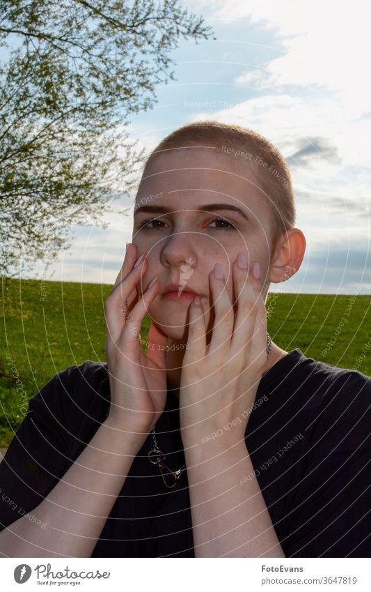 Junge Frau mit sehr kurzem Haar, Hände im Gesicht, steht in der Natur Porträt krank Medizin Mode Tag Schönheit Nägel Krebs attraktiv Mädchen Therapie wirklich