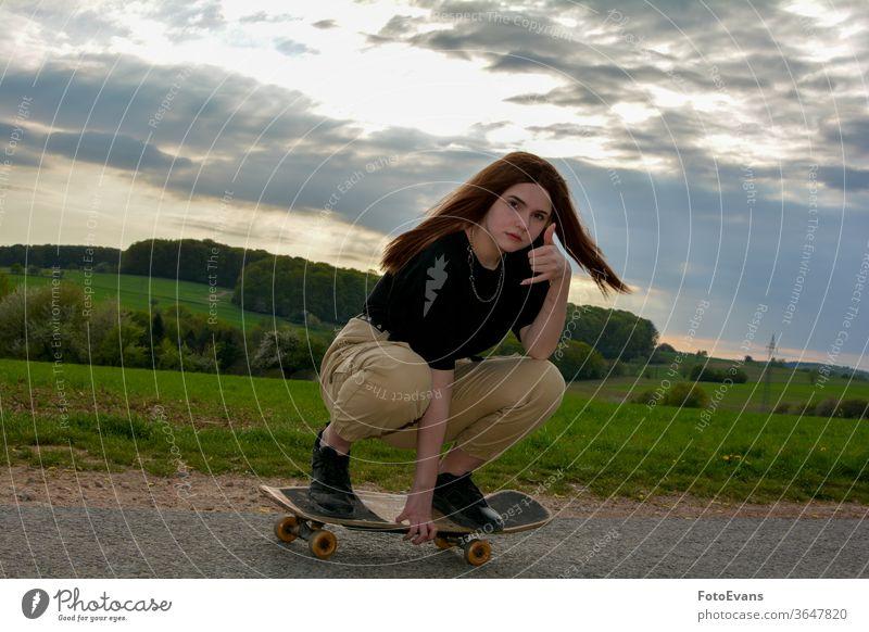 Junges Mädchen läuft Schlittschuh auf einer Straße in der Natur Training sportlich genießend Mode Tag Schönheit Schlittschuhlaufen Hand Frau attraktiv wirklich