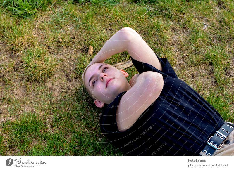 Mädchen mit sehr kurzem Haar liegt im Gras, Arme im Nacken und Kopf Porträt krank Natur Medizin Mode jung Schönheit Krebs Boden Frau attraktiv Therapie wirklich