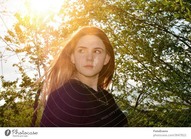 Mädchen steht im Freien mit Baum und Sonnenuntergang Porträt Natur Person Tag Schönheit Frau attraktiv wirklich echte Person Behaarung kahl Sonnenaufgang weich