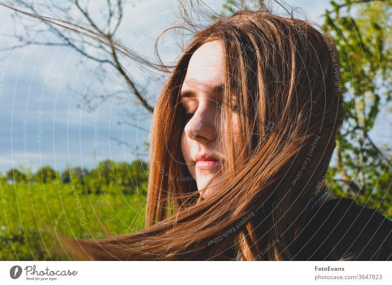 Mädchen steht mit geschlossenen Augen im Sonnenlicht Porträt genießend Natur Mode Tag Schönheit modern attraktiv Baum zugeklappt Stil Behaarung Teenager Person