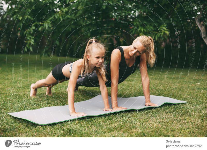 Mutter und Tochter treiben auf dem grünen Rasen in der Nähe ihres Zuhauses Sport. Sport und Fitness im Freien. Gesunde sportliche Lebensweise Yoga Lifestyle