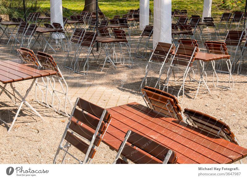 leere Stühle und zusammengeklappte Tische in einem Biergarten Korona Krise Verhaltensregeln Regeln Ausgehverbot soziale Distanz Restaurant Sonnenschirme