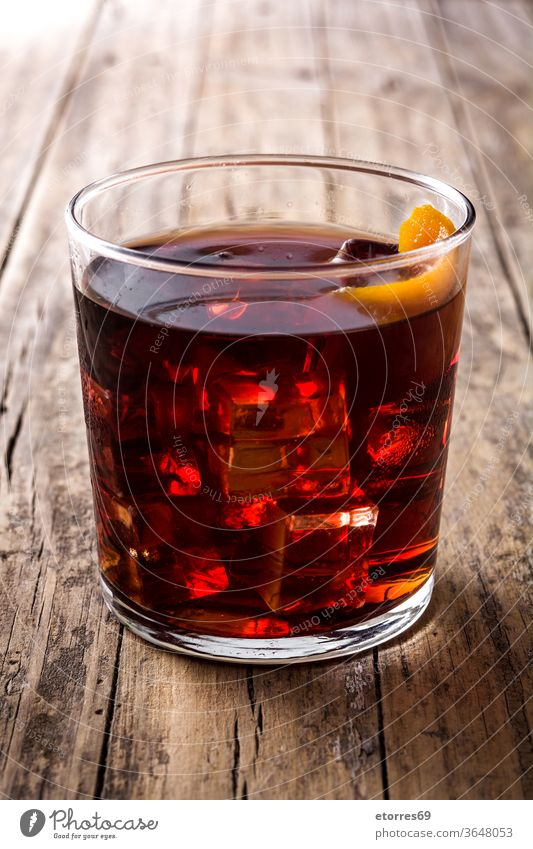 Boulevardier-Cocktail aus Glas auf Holztisch alkoholisch Getränk boulevardier campari kalt trinken Eleganz frisch Frucht Eis mischen orange rot rustikal