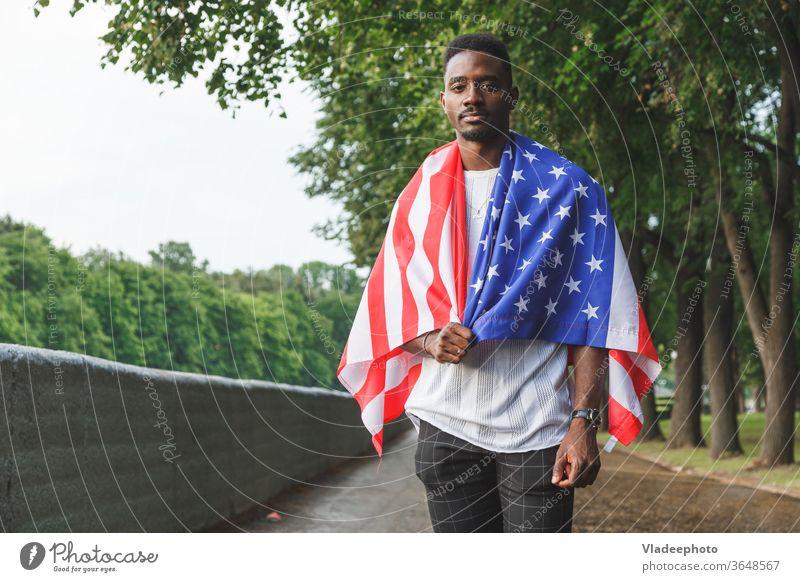 Gutaussehender afroamerikanischer Mann mit der USA-Flagge auf den Schultern, der ernsthaft in die Kamera schaut und im Freien steht. Tag Sommer Amerikaner