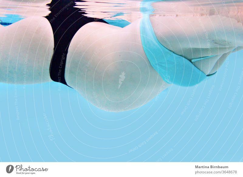 Schwangere Frau mit Babybauch schwimmt in einem Pool, Unterwasserfang unter Wasser Bauch Mutterschaft Schwangerschaft schwanger Herz Schwimmsport Bikini Sommer