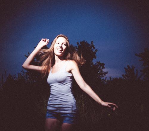 Unscharfes, körniges Foto einer jungen Dame, die in der Nacht extatisch tanzt Mädchen springt ekstatisches Ballett fröhliche Dame springen Junge Frau