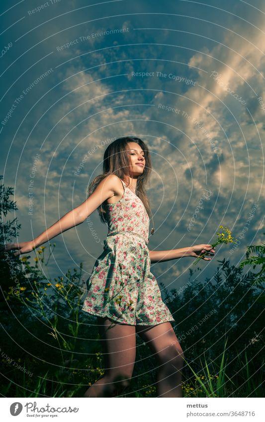 Glückliches Mädchen rennt in der Nacht mit gelben Wildblumen in der linken Hand über die Sommerfelder Beine Tanzen Teil von Körper Kleid springen aktiv Frau