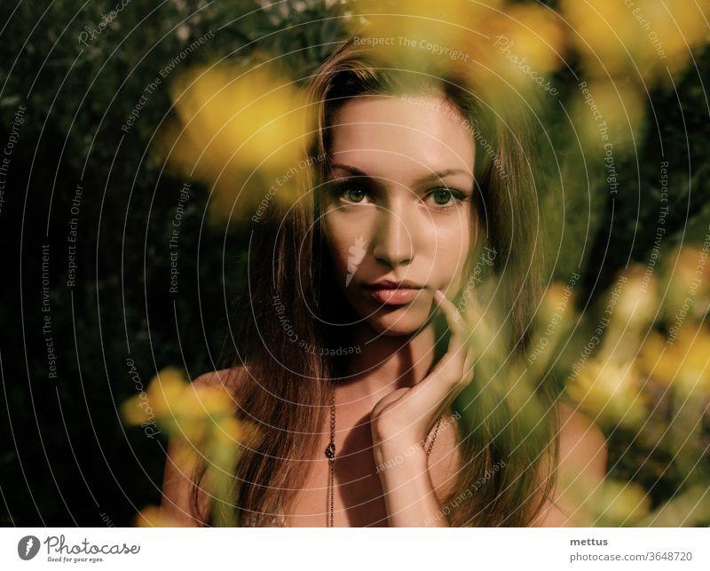 Nachdenkliche Blondine in einem Sommerfeld mit verschwommenen Blumen im Vordergrund, Fokus auf das Gesicht blond Kleid Schnappschuss schön Feld Mode Frühling