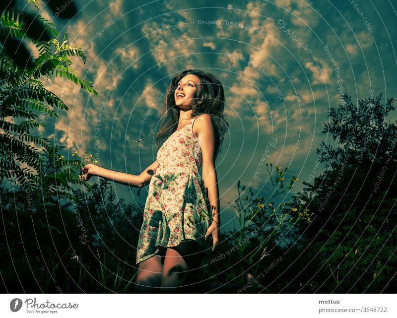 Ein fröhliches Mädchen tanzt im hohen Gras vor dem dramatischen Himmel. Hochsprung in Frühlingsfeldern. Sie ist in ein leichtes Sommerkleid gekleidet. Tanzen