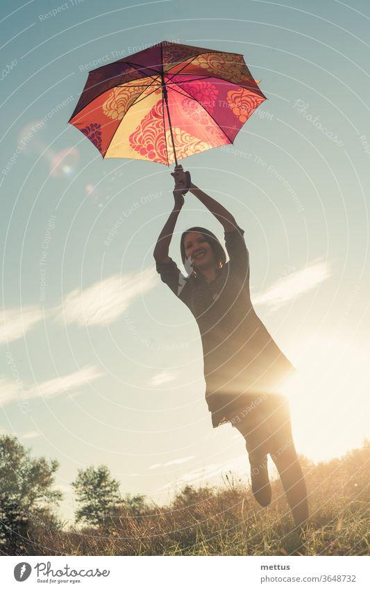 Ein junges körperpositives Mädchen tanzt bei Sonnenuntergang mit einem farbigen Regenschirm auf einer von der Sonne beleuchteten Wiese. Frau Freiheit Glück frei