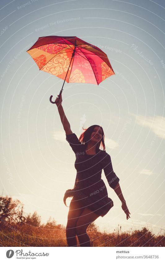 Fröhliche Dame tanzt fröhlich mit rotem Regenschirm im Licht des Sonnenuntergangs auf den Feldern. Frau Freiheit Glück frei Kleid Emotion klassisch Person Bild