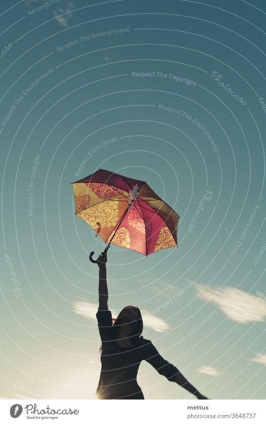 Mädchensilhouette gegen den Himmel streckt sich mit einer Hand, in der sie einen Regenschirm hält, nach oben Frau Freiheit Glück frei Kleid Emotion klassisch