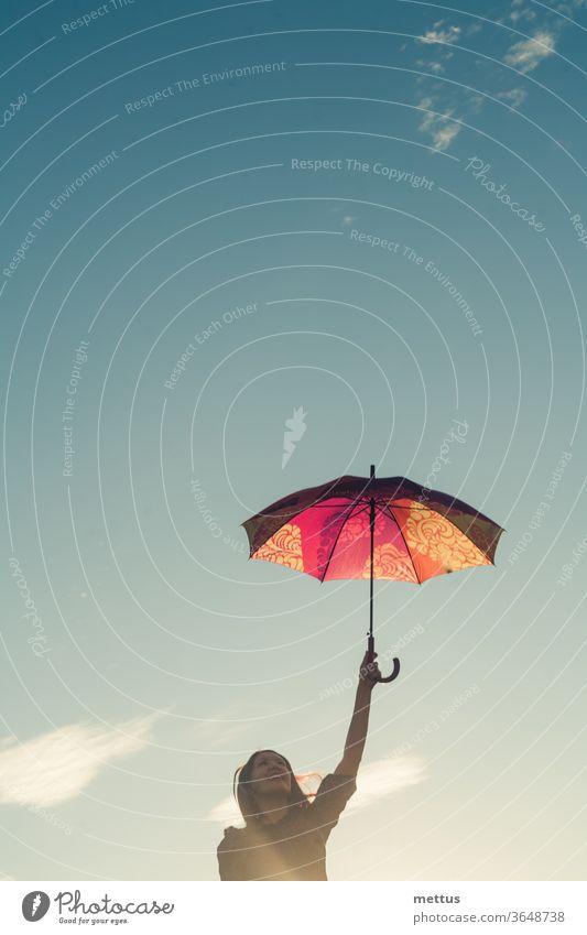 Fröhliches Mädchen hält bunten Regenschirm in den Händen vor dem Himmel mit Raumwolken, viel Kopierraum Frau Freiheit Glück frei Kleid Emotion klassisch Person