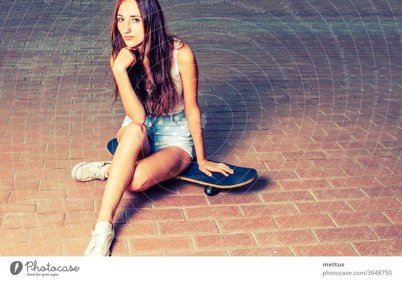 Sportliche Frauen mit langen roten Haaren sitzen auf Skateboaed Mädchen Spaß jung Jugend aktiv Skateboarding Skater Menschen Behaarung schön Schönheit lässig