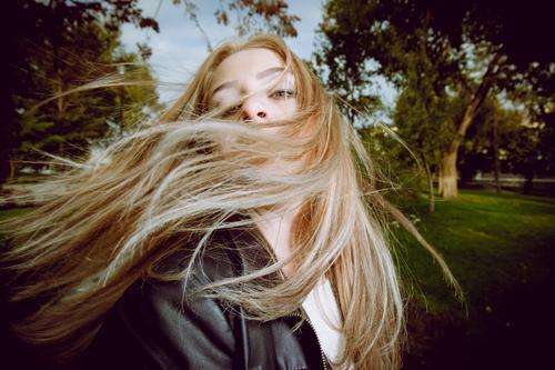 Blondhaarige Dame posiert im Park und tanzt mit ihrem langen blonden Haar in der Luft im Freien Menschen Natur Porträt Erholung Erwachsener Mode niedlich Kind