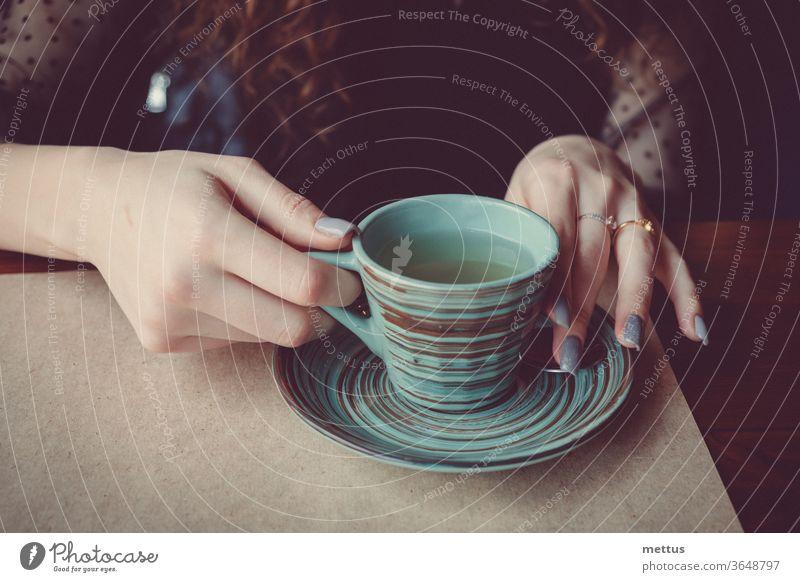 Vintage-Foto der Hände des Mädchens, das eine anmutige Keramiktasse hält, die mit einem Muster aus farbigen Kreisen bedeckt ist Frau Sitzen trinken Beteiligung