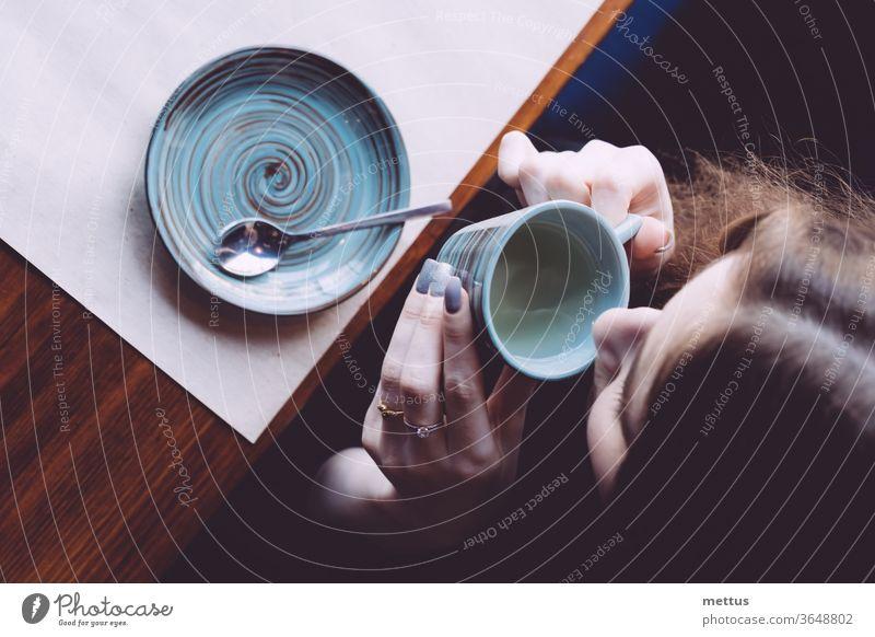 Blick von oben auf ein Mädchen, das aus einer kleinen Tasse Tee trinkt. obere Ansicht Heißgetränk Nostalgie Person Frau Sitzen Oberseite des Kopfes Einsamkeit